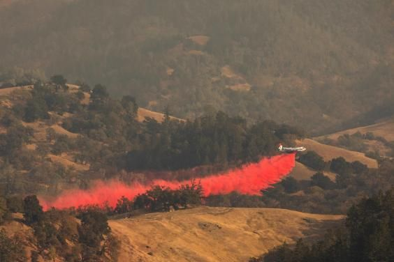 An air tanker drops fire retardant in the valley below in Healdsburg, California, on 26 October 2019 (AFP/Getty)